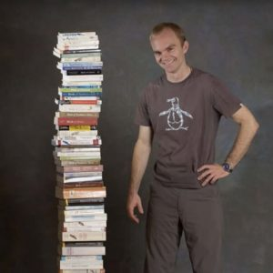 Noah Strycker with stack of field guides